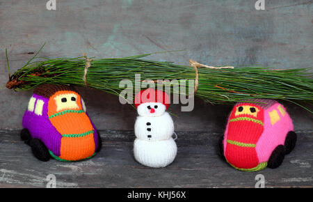 Two car transport pine tree for Xmas decoration, knitted colorful cars on wooden, snowman standing beside make funny - Stock Photo