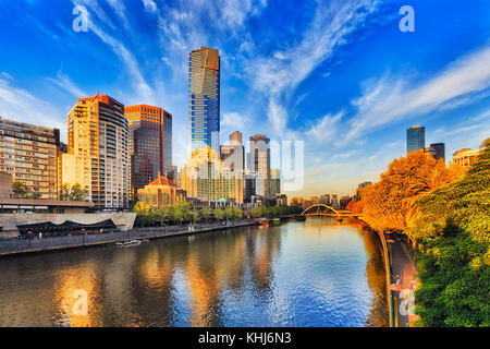 Tallest Melbourne skyscraper Eureka tower dominates South Yarra cityscape over Yarra river in warm morning sunlight - Stock Photo
