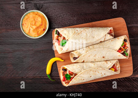 Mexican burritos with cheese salsa, chili peppers, and copyspace - Stock Photo
