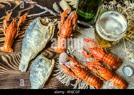 Beer in a glass and a bottle of beer with a snack of boiled crawfish and dried salted fish on dark wood boards - Stock Photo
