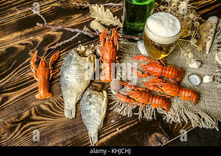 Dried salted fish  and beer with foam in glass  and with boiled red crayfish on canvas, lying on dark wood boards - Stock Photo