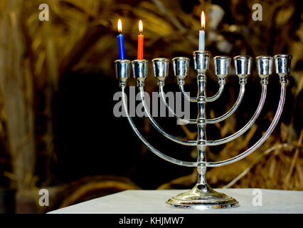 A Chanukia the main symbol of Chanukah, The Jewish festival of light with 3 lit candles for the second day - Stock Photo