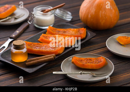 Baked slices of pumpkin with honey and sugar on wooden background. healthy dessert. selective focus. - Stock Photo