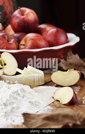 Old wooden rolling pin dusted with white flour over a rustic table. Apple pie ingredients of apples and butter in - Stock Photo