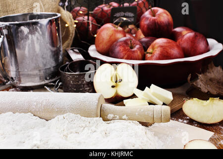 Old wooden rolling pin dusted with white flour over a rustic table. Apple pie ingredients of apples and butter with - Stock Photo