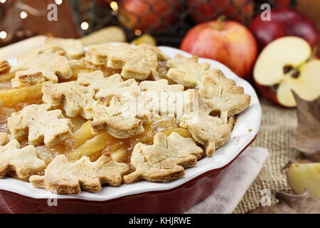 Freshly baked apple pie with top crust cut into autumn leaves shape. Apples in background. - Stock Photo