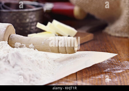 Old wooden rolling pin dusted with white flour over a rustic table. Butter and measuring cups in background. Shallow - Stock Photo