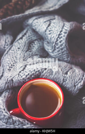 Winter background - hot tea in red cup and gray woolen scarf - Stock Photo