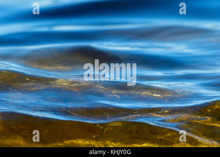 A close up image of some ocean waves rippling into shore on Vancouver Island British Columbia Canada. - Stock Photo