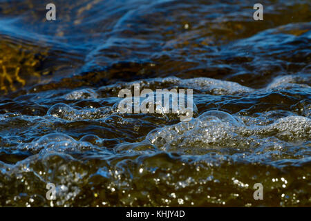 A close up image of some ocean waves rippling into shore creating some bubbles on Vancouver Island British Columbia - Stock Photo