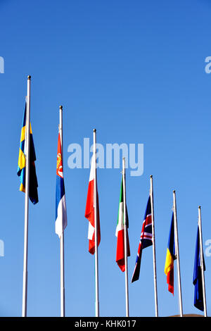the flags of the European nations on flagpoles in various colours. Banners and emblems of different states and countries. - Stock Photo