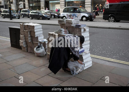 A woman stoops near bundles of Evening Standard newspapers in Piccadilly, on 9th November 2017, London, England. - Stock Photo