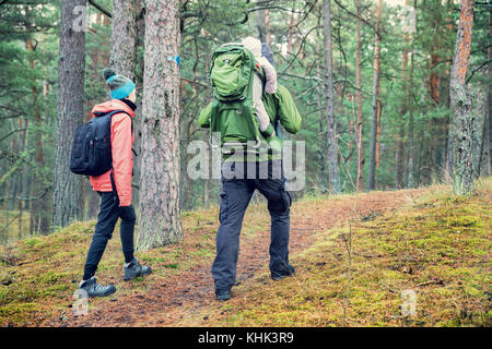 family walking forest trail with baby in child carrier on father's back - Stock Photo