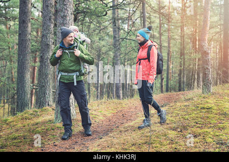 family hiking in the forest with baby in child carrier - Stock Photo
