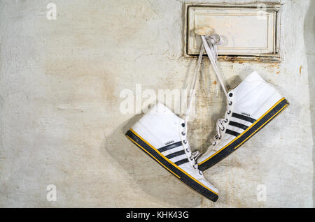 Minsk, Belarus - September 29, 2017: White Adidas Sneakers Hang on Laces and Dry on a Russian Stove, Close-up - Stock Photo