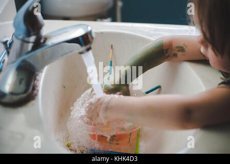 A toddler girl washing paint off her hands in a bathroom sink. - Stock Photo