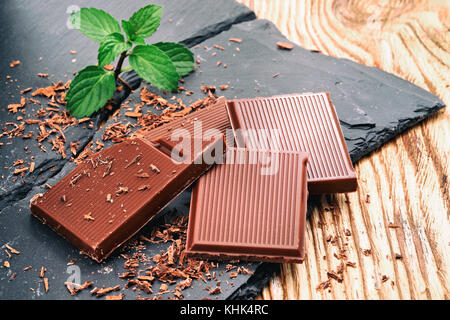 Broken dark chocolate and chocolate flakes on a wooden table - Stock Photo