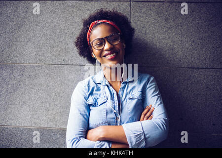 Stylishly dressed young African woman laughing while standing with her arms crossed against a wall listing to music - Stock Photo