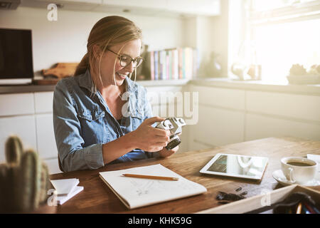 Young female photographer looking at images on her camera while working on her small business at home - Stock Photo
