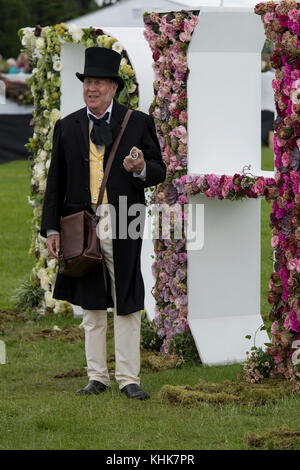 Man talking, is dressed in Victorian outfit & standing by giant floral RHS letters - RHS Chatsworth Flower Show - Stock Photo