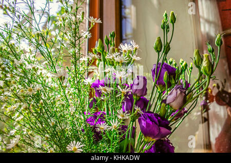 Bouquet of purple flowers Lisianthus with branches delicate white wildflowers on the windowsill in bright sunny - Stock Photo