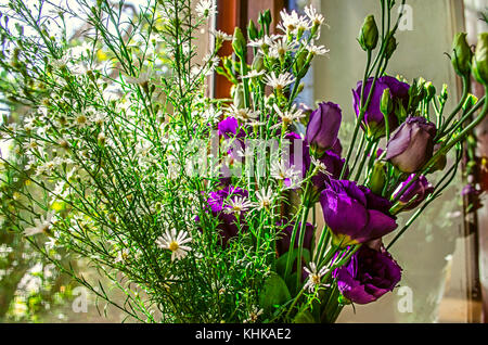 Purple flowers Lisianthus and branches delicate white wildflowers on the windowsill on a bright sunny day - Stock Photo