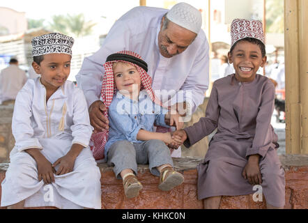 Nizwa, Oman, 10th Nobember 2017: omani kid and european kid shaking hands - Stock Photo