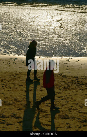 Two people or a man and a woman couple walking along a beach at sunset in silhouette against the sea reflecting - Stock Photo