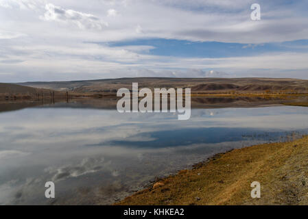 Scenic autumn landscape with beautiful lake in the desert with rare vegetation on the banks on a background of mountains, - Stock Photo