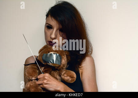 A demon female trying to kidnap and kill a teddybear - Stock Photo