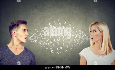 Language barrier concept. Handsome man talking to an attractive young woman with many questions - Stock Photo