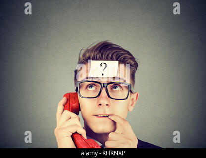 Perplexed young man with question mark having a telephone conversation - Stock Photo
