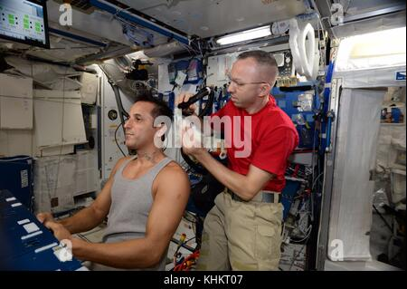 Expedition 53 American astronaut Randy Bresnik, right, gives a hair cut to astronaut Joe Acaba aboard the International - Stock Photo