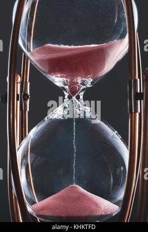 Hourglass with sand in red color and glass body stuck by metal frame. - Stock Photo