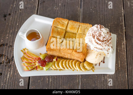 Honey Toast with vanilla ice-cream, grape, kiwi, banana, apple and whip cream - Stock Photo