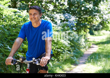 Mature Man Cycling Along Path In Countryside - Stock Photo