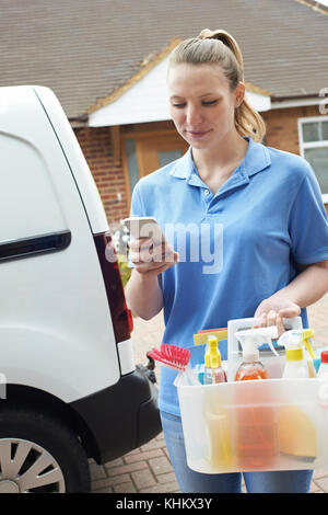 Woman Running Mobile Cleaning Business With Van Checking Text Message On Mobile Phone - Stock Photo