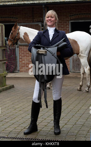 Attractive blond woman holding a black leather saddle with her Skewbald horse. In a stableyard. November 2017 - Stock Photo