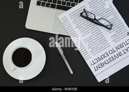Overhead of cup of coffee, laptop, spectacles, newspaper and pen on black background - Stock Photo