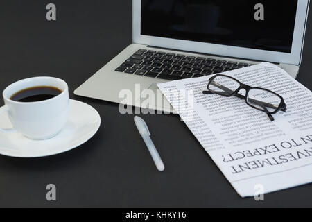 Close-up of coffee cup, laptop, spectacles, newspaper and pen on black background - Stock Photo