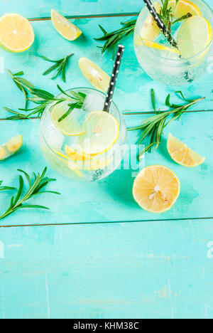 Cold lemonade or alcohol vodka cocktail with lemon and rosemary, on light blue table, copy space - Stock Photo