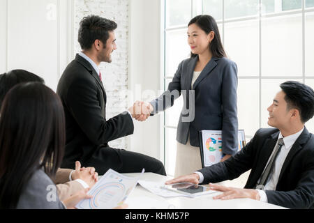 Successful job Asian businessman and businesswoman shaking hands in board room when finishing up a meeting. - Stock Photo