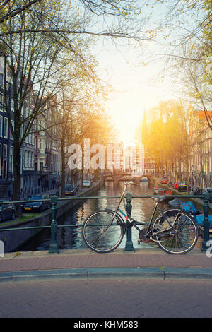 Bicycle on the bridge with Netherlands traditional houses and Amsterdam canal in Amsterdam ,Netherlands. - Stock Photo