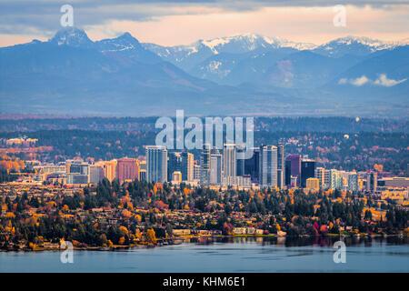 Bellevue Washington. The snowy Alpine Lakes Wilderness mountain peaks rise behind the urban skyline. - Stock Photo