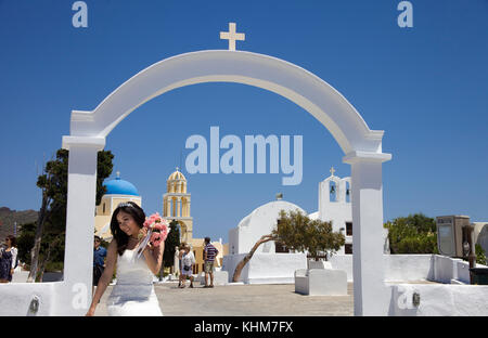 Bridal with bridal bouquet posing at orthodox church, Oia, Santorin island, Cyclades, Aegean, Greece - Stock Photo