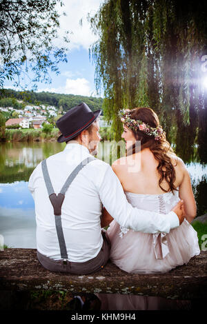 Photo of a young couple soon to be married, sitting on a bench beside a lake and beautiful country scenery. - Stock Photo