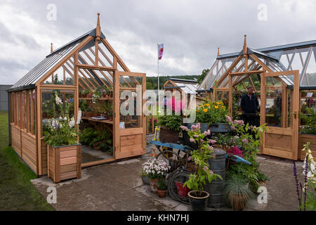 People at Gabriel Ash trade stand, viewing timber greenhouses on display & for sale - RHS Chatsworth House Flower - Stock Photo