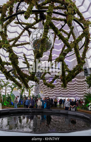 People view Heart of Glass glitter ball hanging in moss-covered framework - centre of inflatable marquee at Chatsworth Flower Show, Derbyshire,GB, UK.
