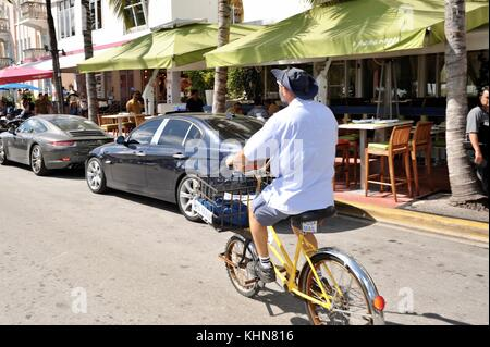 United States Post Office (USPS) postal worker, postman, delivering mail on bicycle in South Beach, Miami, Florida, - Stock Photo