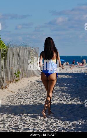 beautiful tanned woman in bikini walking back toward beach and ocean khn84c